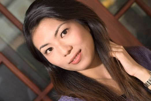 Asian woman portrait with black hair and yellow skin.