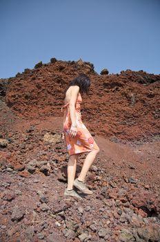 woman walking on volcanic rokcs