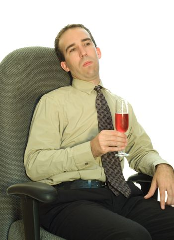 A young businessman looking bored, while he sits in his chair drinking wine