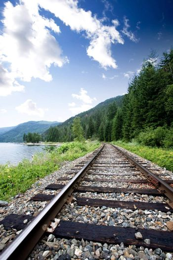 Train tracks near a large lage going through the mountains
