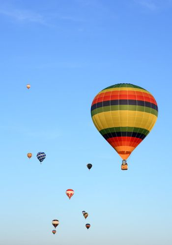 Many colorful hot air balloons in the blue sky.