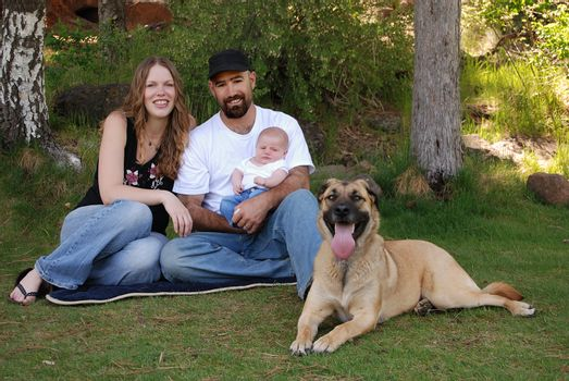 Horizontal image of a young modern family of three and their dog resting in the park.