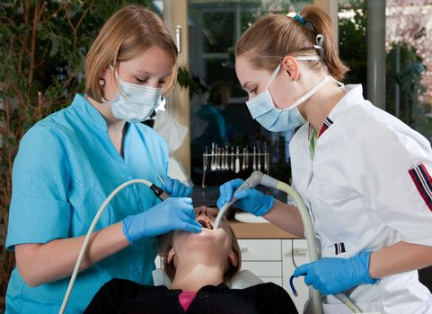 Female dentist working on her patient with her assistent
