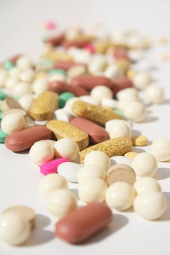 Various pills against white background with shallow depth of field on midground