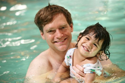 Father and toddler boy swimming in pool