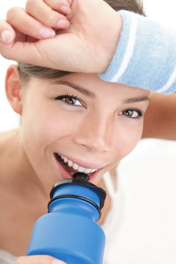 Fitness woman close-up. Sport woman with sweatband drinking water from blue sport bottle.