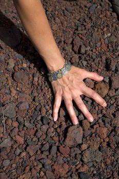 hand on volcanic stones