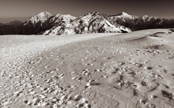 Mountain scenic with foot steps on snow land.