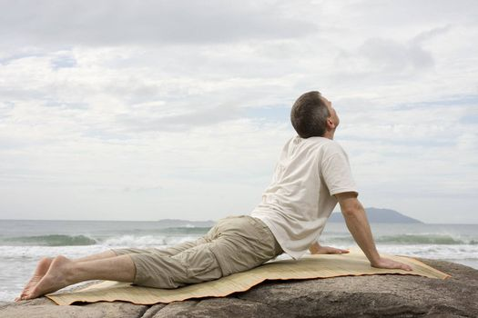 Mature man doing yoga exercises on a rock at the sea