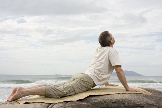 Mature man doing yoga at the sea