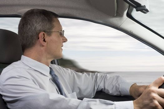 Businessman driving a car at the sea