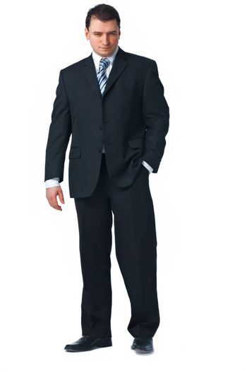 Full length of a confident young business man standing against white with one hand in his pocket