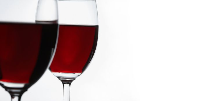 Red wine on white background. Focus is on the second glass