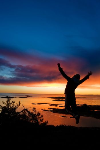 A person jumping by the ocean raising their arms in celebration with slight motion blur on the hands.