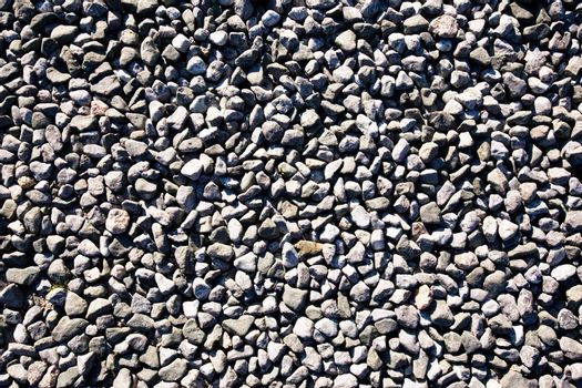 A small stone background texture of smooth stones near the ocean.