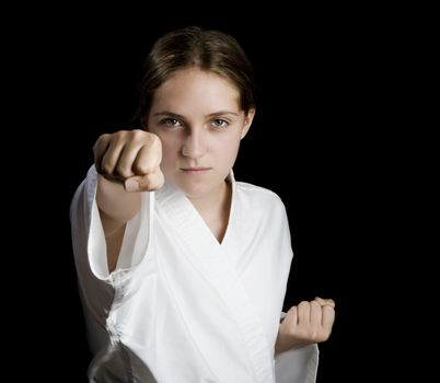 Pretty young girl in karate pose on black background