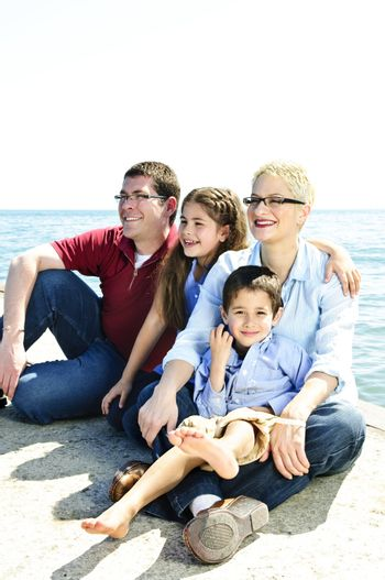 Happy family sitting on pier at lake