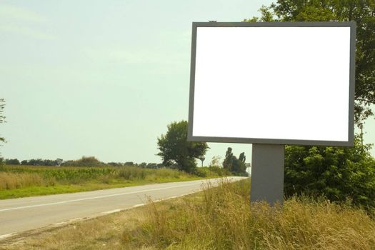 Deserted road with white billboard