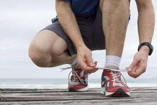 Runner tying shoelace in front of the sea