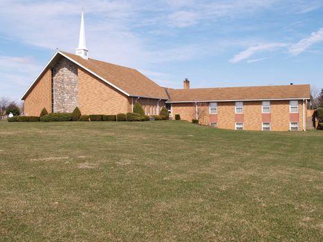 modern brick church building with a grass lawn