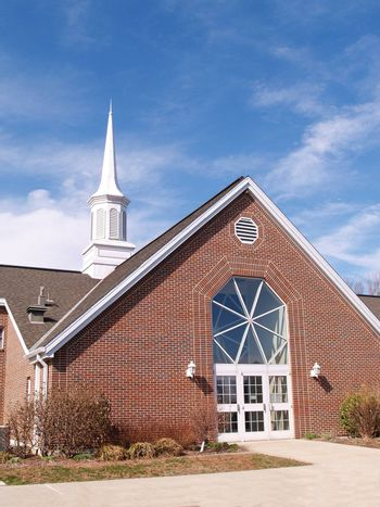 red brick modern church with a white steeple and blue sky background