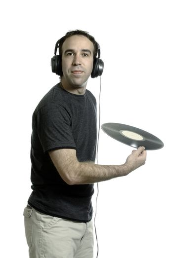 A young man wearing a set of headphones about to throw away an old LP record, isolated against a white background