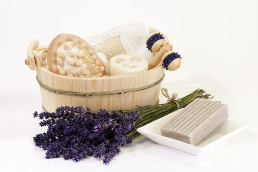 Lavender, flask of oil and massage supplies on white background