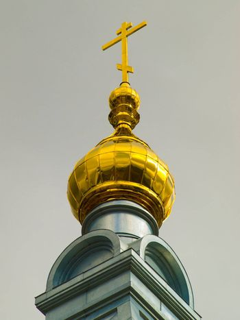 A golden dome with a cross of christian temple