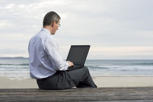 Businessman working with laptop on a beach