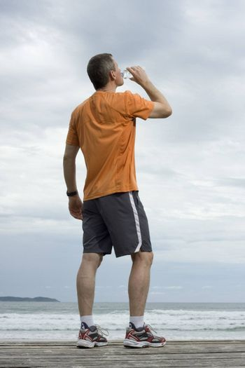 Mature runner drinking water on a beach