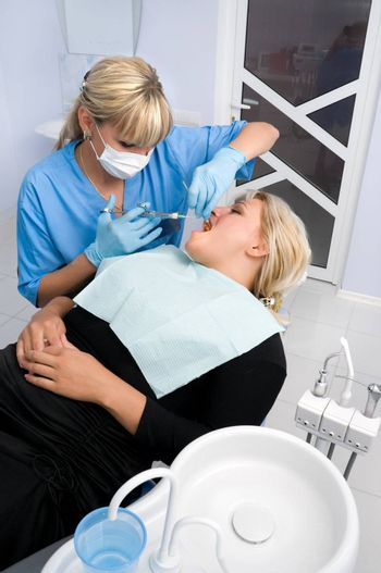 female dentist works with patient the office
