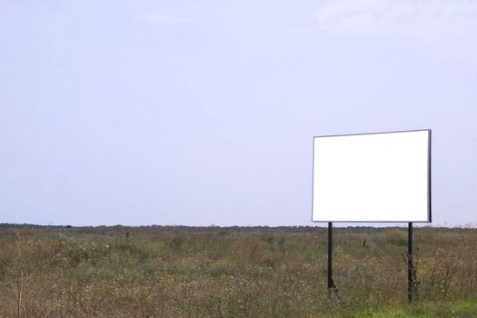 Empty field with white billboard on side of frame