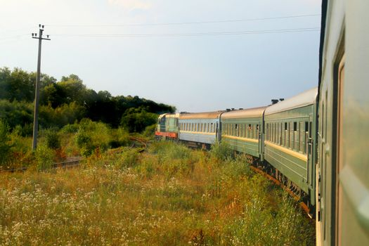 Eastern european train entering into a forested area of track