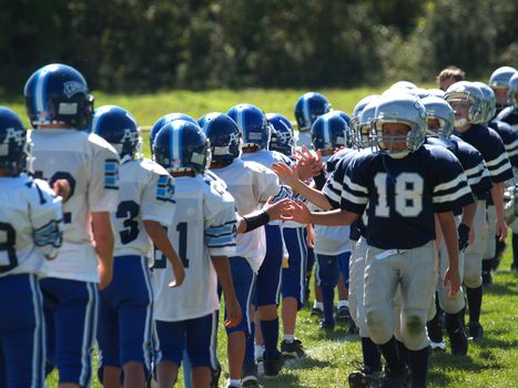 Young American football teams displaying sportsmanship at the end of the game.