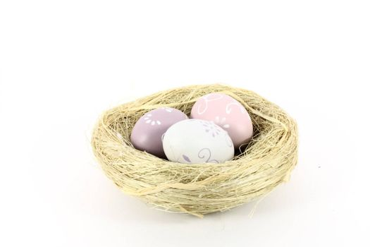 A bird nest with colored eggs isolated on white