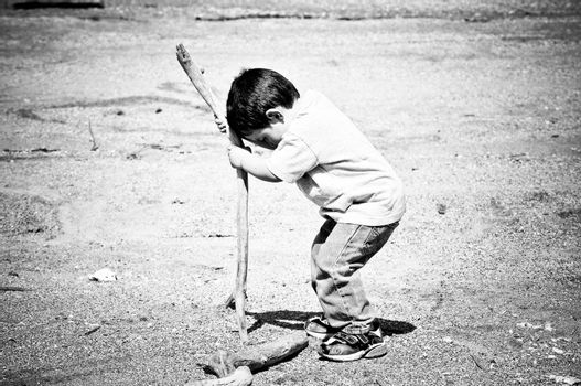 Boy Playing With Stick in the Sand