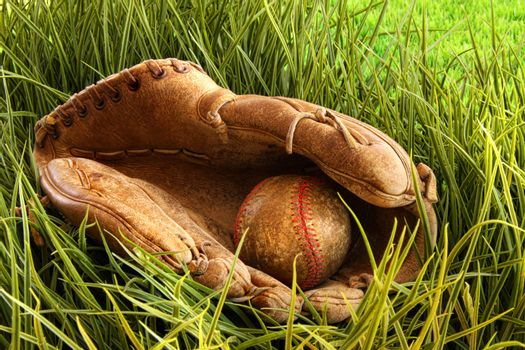 Old baseball glove with ball in the grass