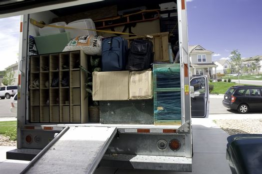 Packing up the box truck with household belongings, ready to travel and move.
