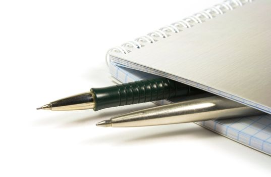 blank notebook and two pens