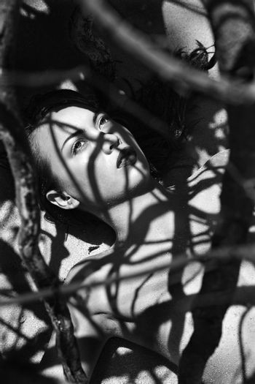 Pretty Filipino nude young woman on beach in tree shadows in Maui, Hawaii.