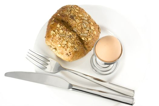 bun, egg, cutlery and a white plate