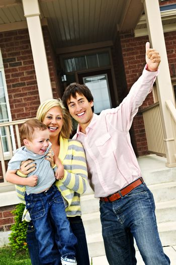 Young excited family celebrating in front of new home