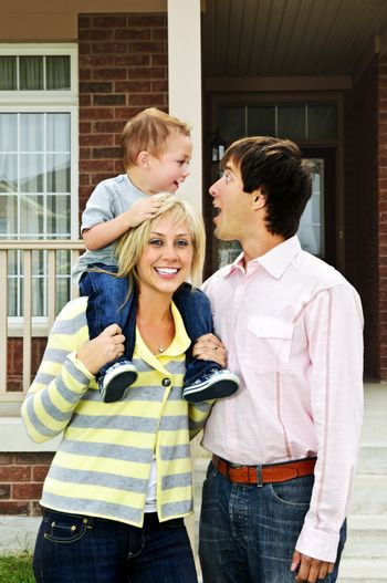 Young happy family standing in front of new home