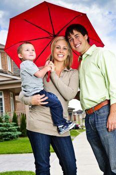 Young happy family under umbrella on sidewalk