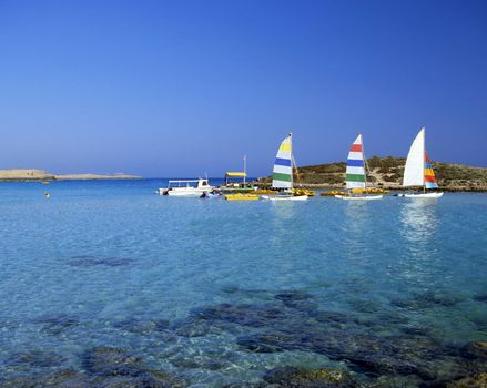 Bright pleasure sailboats by rocks in the shallow water of Nissi Beach, Cyprus