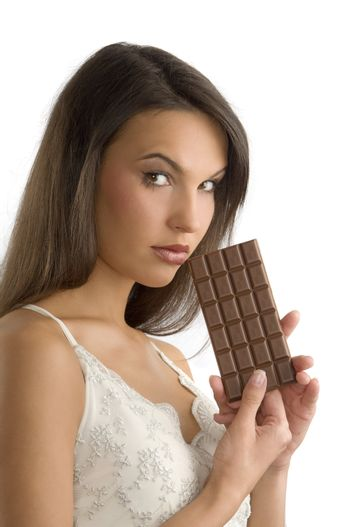 cute brunette with a block of chocolate in her hands looking in camera