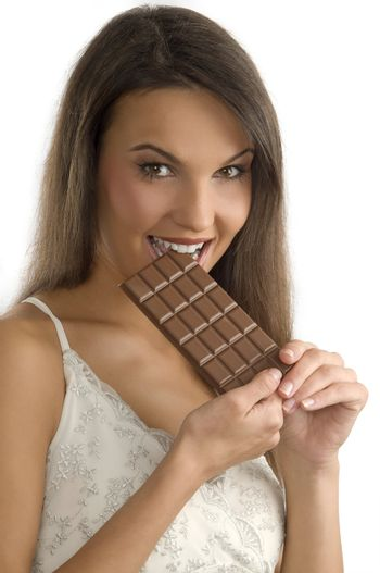 pretty young brunette biting a block of chocolate with her teeth