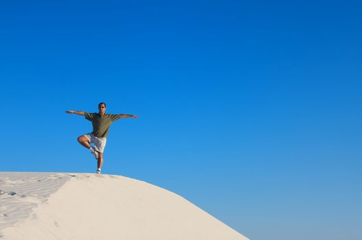 Man in a red shirt with his arms raised in a yoga tree pose looking off into the distance on top of a white sand dune with a blue sky