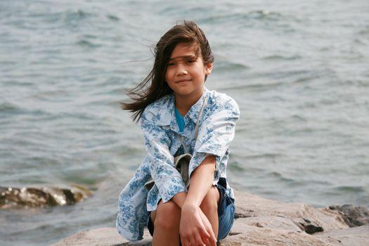 Nine year old girl sitting by lake