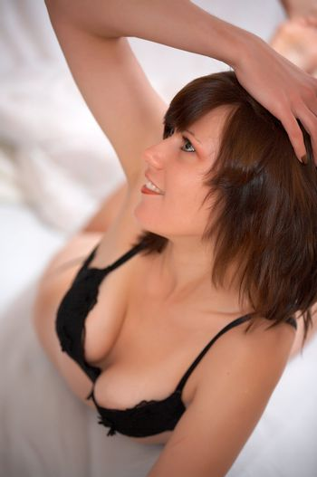 Young beautiful woman lies on bed with smile